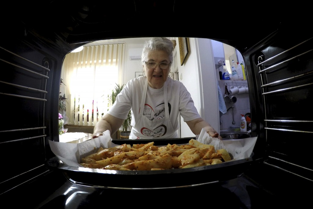 Jelena Petrovic places the tray with food into the oven in her home in Jagodina, Serbia, Tuesday, Feb. 12, 2019. Serbs looking for ideas are increasin