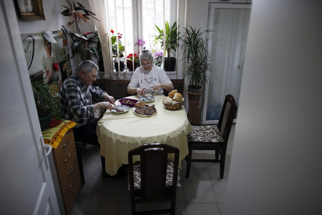 Jelena Petrovic, center, and her husband Milan having a lunch in their home in Jagodina, Serbia, Tuesday, Feb. 12, 2019. Serbs looking for ideas are i