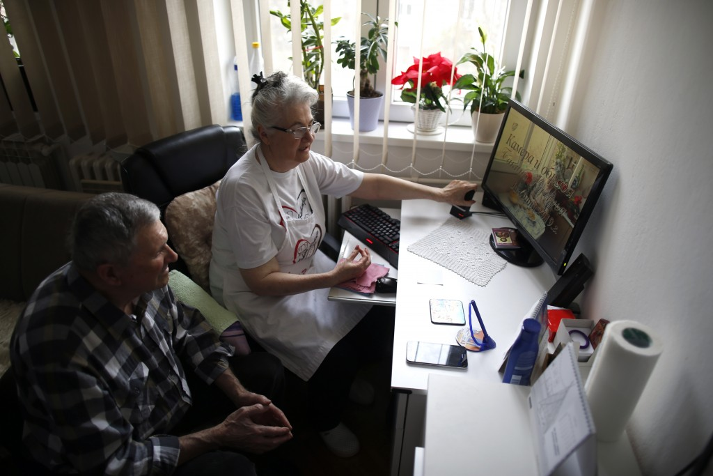 Jelena Petrovic, left, and her husband Milan watch her YouTube channel in their home in Jagodina, Serbia, Tuesday, Feb. 12, 2019. Serbs looking for id...