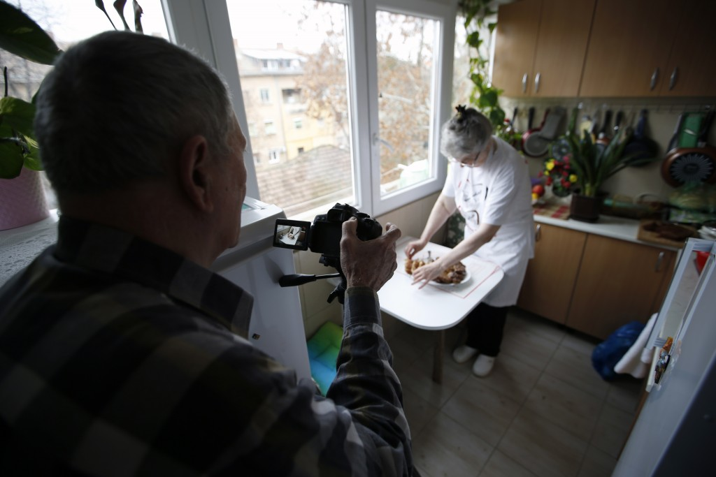 Jelena Petrovic's husband Milan records preparing the food in her home in Jagodina, Serbia, Tuesday, Feb. 12, 2019. Serbs looking for ideas are increa