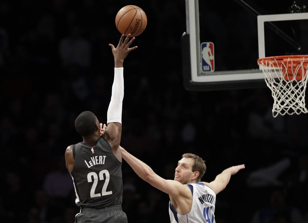 Dallas Mavericks forward Dirk Nowitzki (41) defends as Brooklyn Nets guard Caris LeVert (22) shoots during the first half of an NBA basketball game, M...