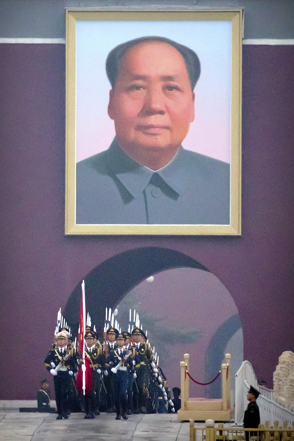 A Chinese honor guard marches out beneath the large portrait of Chinese leader Mao Zedong to perform the daily flag raising ceremony at Tiananmen Squa...