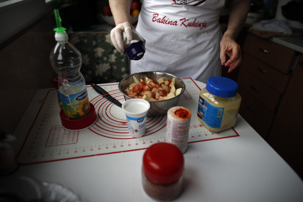 Jelena Petrovic prepares the food in her home in Jagodina, Serbia, Tuesday, Feb. 12, 2019. Serbs looking for ideas are increasingly turning to the Bal...
