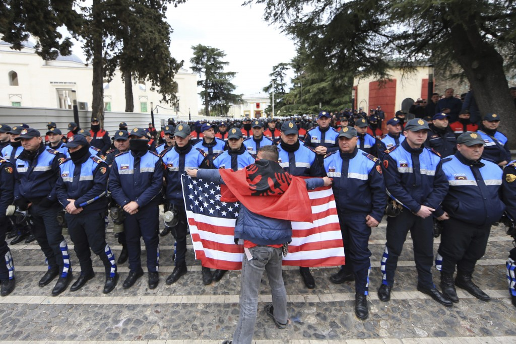 A protester who is covered with an Albanian flag holds a US in front of Albanian policemen guarding the parliament building as opposition supporters t