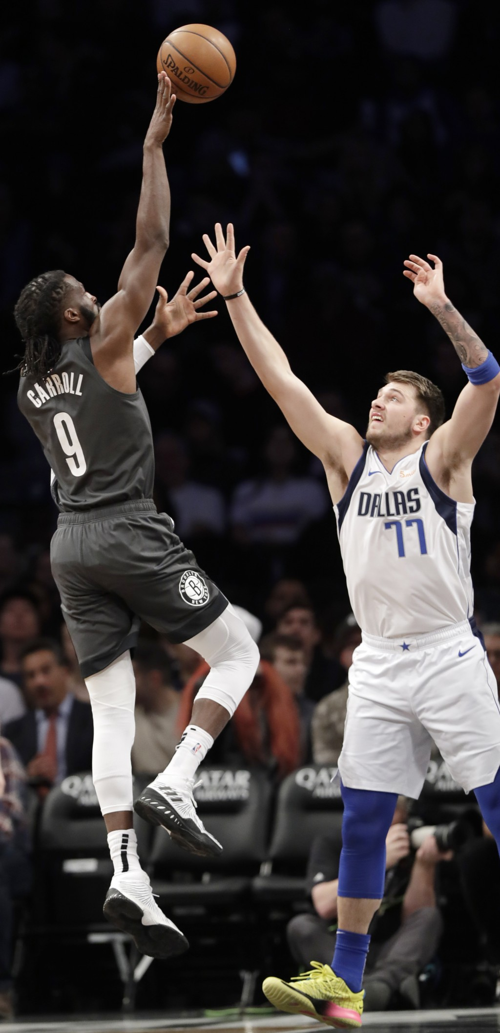 Brooklyn Nets forward DeMarre Carroll (9) shoots a three-point basket with Dallas Mavericks forward Luka Doncic (77) defending against him during the