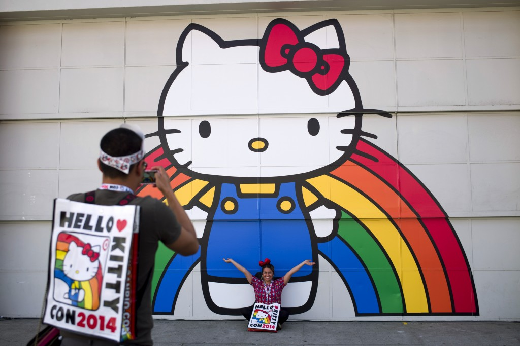 FILE - In this Oct. 30, 2014, file photo, Keith Nunez, left, takes pictures of his wife, Carolina, at the first-ever Hello Kitty fan convention, Hello
