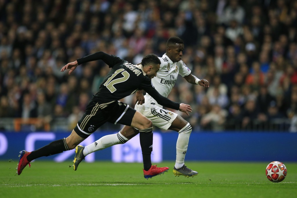 Ajax's Noussair Mazraoui left tries to stop Real forward Vinicius Junior during the Champions League round of 16 second leg soccer match soccer matc