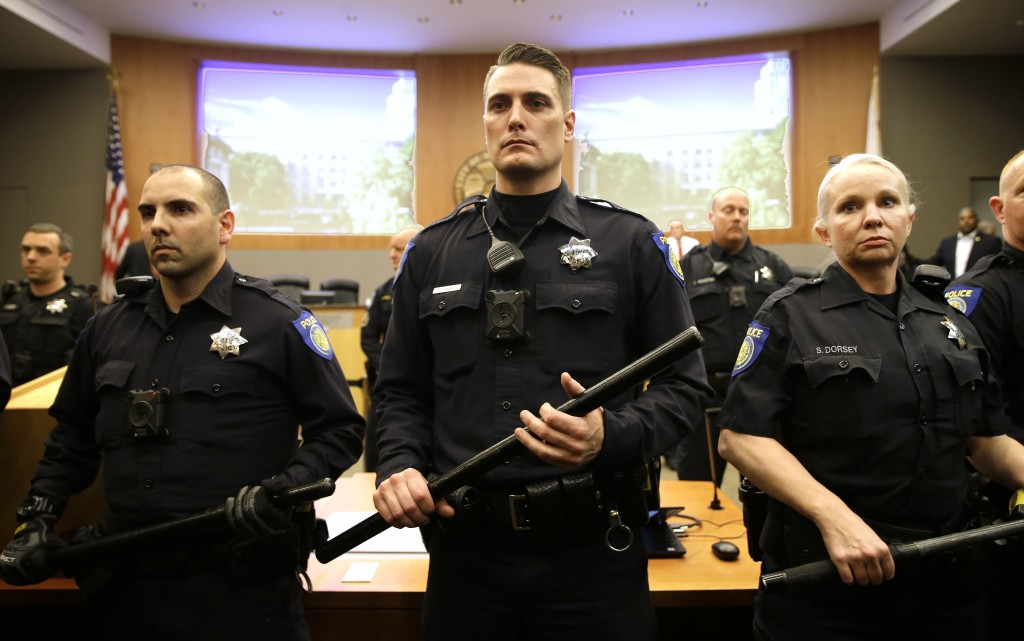 Baton carrying Sacramento Police Officers stand in front of the Sacramento City Council chambers as a disruption breaks out Tuesday, March 5, 2019, in...