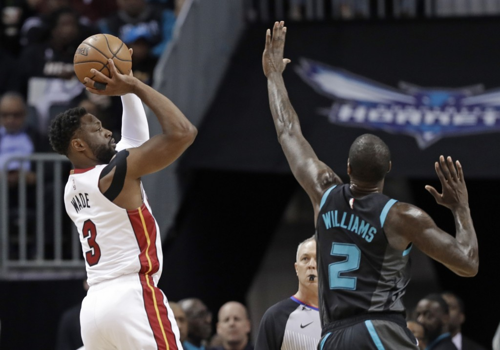 Miami Heat's Dwyane Wade (3) shoots over Charlotte Hornets' Marvin Williams (2) during the first half of an NBA basketball game in Charlotte, N.C., We