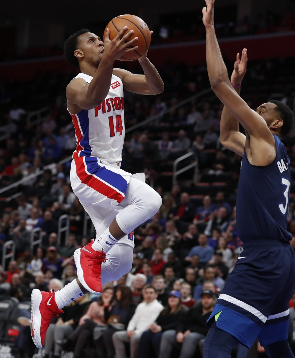 Detroit Pistons guard Ish Smith (14) shoots as Minnesota Timberwolves forward Keita Bates-Diop (31) defends during the first half of an NBA basketball