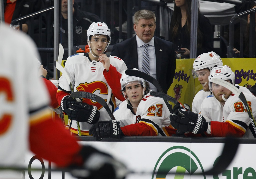 Calgary Flames coach Bill Peters, center right, and Johnny Gaudreau (13) watch from the bench during the first period of an NHL hockey game against th
