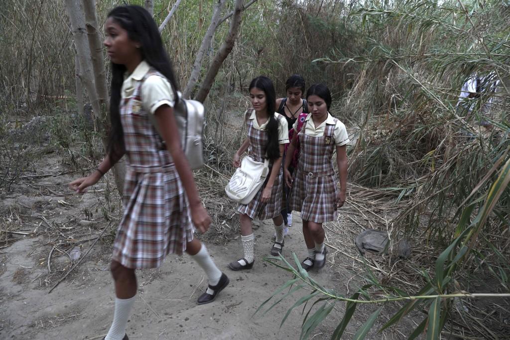 Venezuelan students walk into Colombia from Venezuela along the Tachira River, near the Francisco de Paula Santander International Bridge, Wednesday,