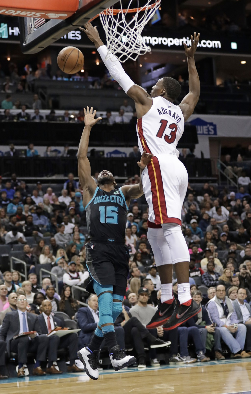 Charlotte Hornets' Kemba Walker (15) tries to shoot over Miami Heat's Bam Adebayo (13) during the first half of an NBA basketball game in Charlotte, N