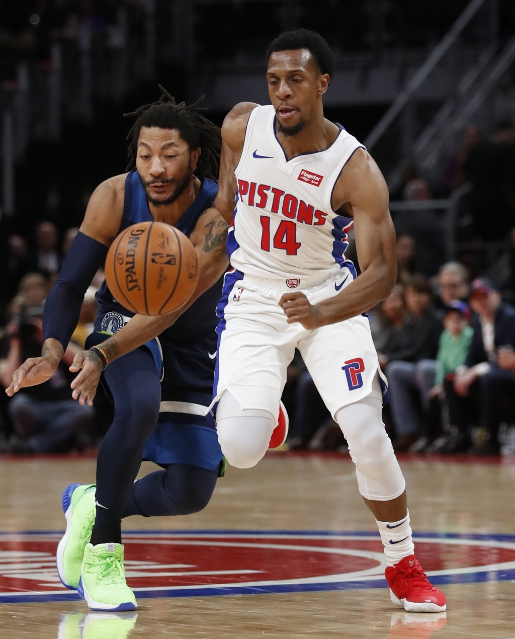 Minnesota Timberwolves guard Derrick Rose and Detroit Pistons guard Ish Smith (14) chase the loose ball during the first half of an NBA basketball gam