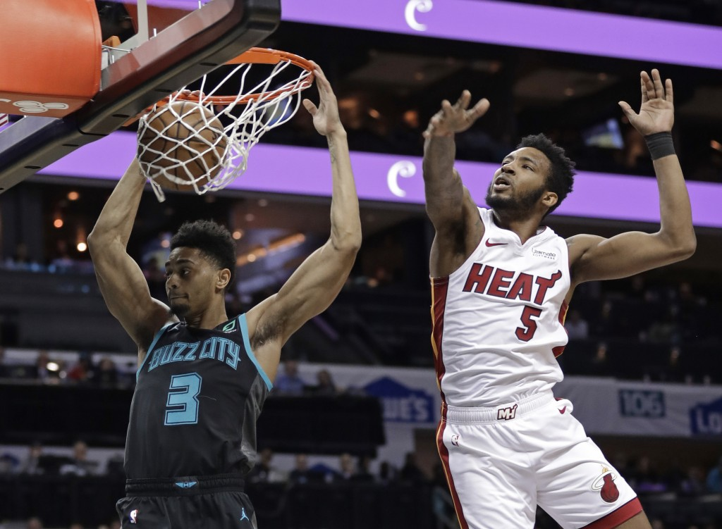 Charlotte Hornets' Jeremy Lamb (3) dunks against Miami Heat's Derrick Jones Jr. (5) during the first half of an NBA basketball game in Charlotte, N.C.