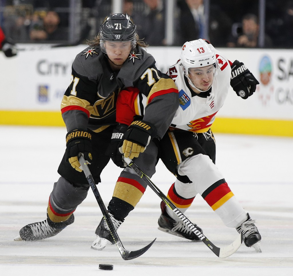 Vegas Golden Knights center William Karlsson (71) and Calgary Flames left wing Johnny Gaudreau (13) vie for the puck during the third period of an NHL