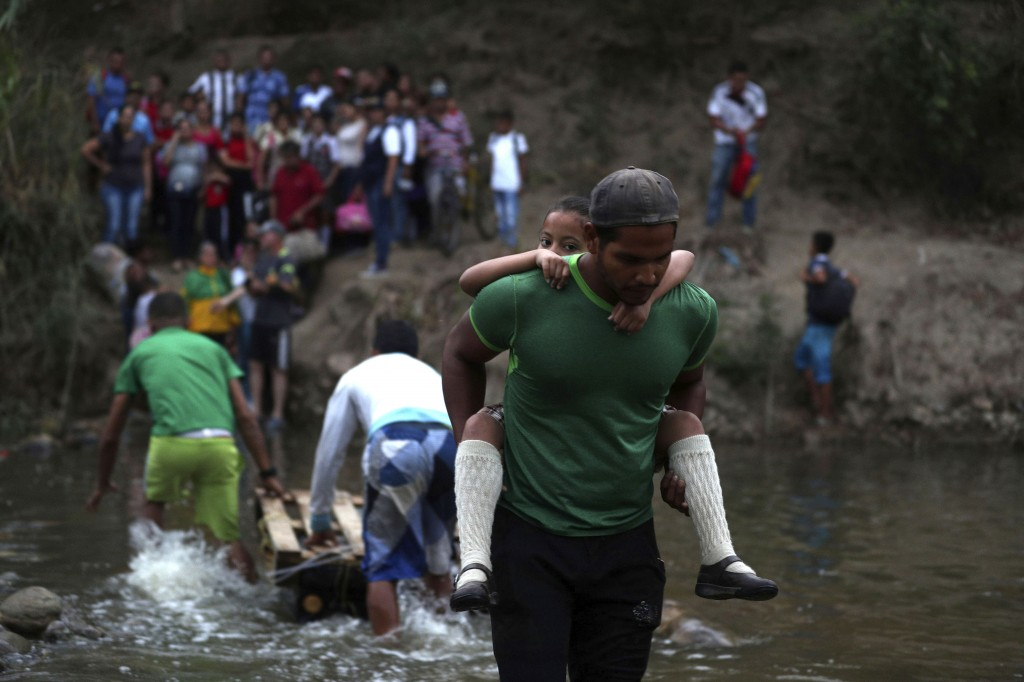 A volunteer gives a Venezuelan student a piggyback ride across the Tachira River into Colombia from Venezuela, near the Francisco de Paula Santander I