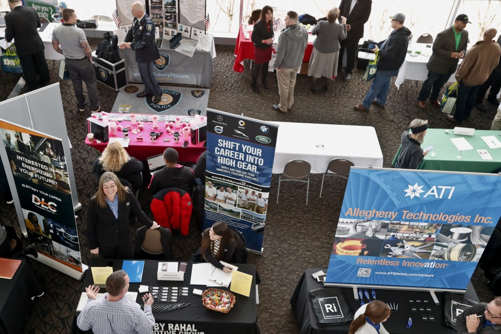 In this Thursday, March 7, 2019, photo visitors to the Pittsburgh veterans job fair meet with recruiters at Heinz Field in Pittsburgh. On Friday, Marc