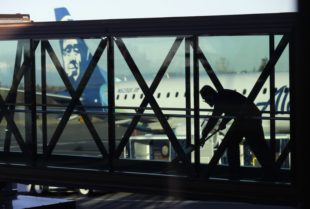 FILE- In this March 4, 2019, file photo a worker cleans a jet bridge before passengers boarded an Alaska Airlines flight to Portland, Ore., at Paine F