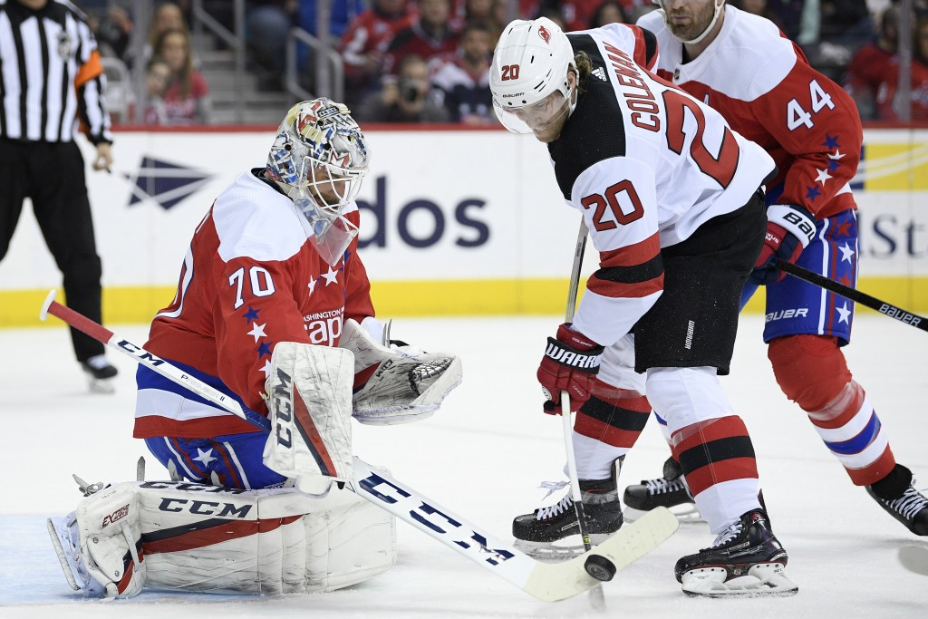 Washington Capitals goaltender Braden Holtby (70) and New Jersey Devils center Blake Coleman (20) reach for the puck during the first period of an NHL