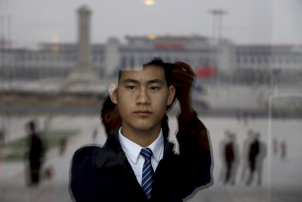 In this March 9, 2019, photo, a security officer stands on duty behind a glass window reflecting Tiananmen Square at the Great Hall of the People wher