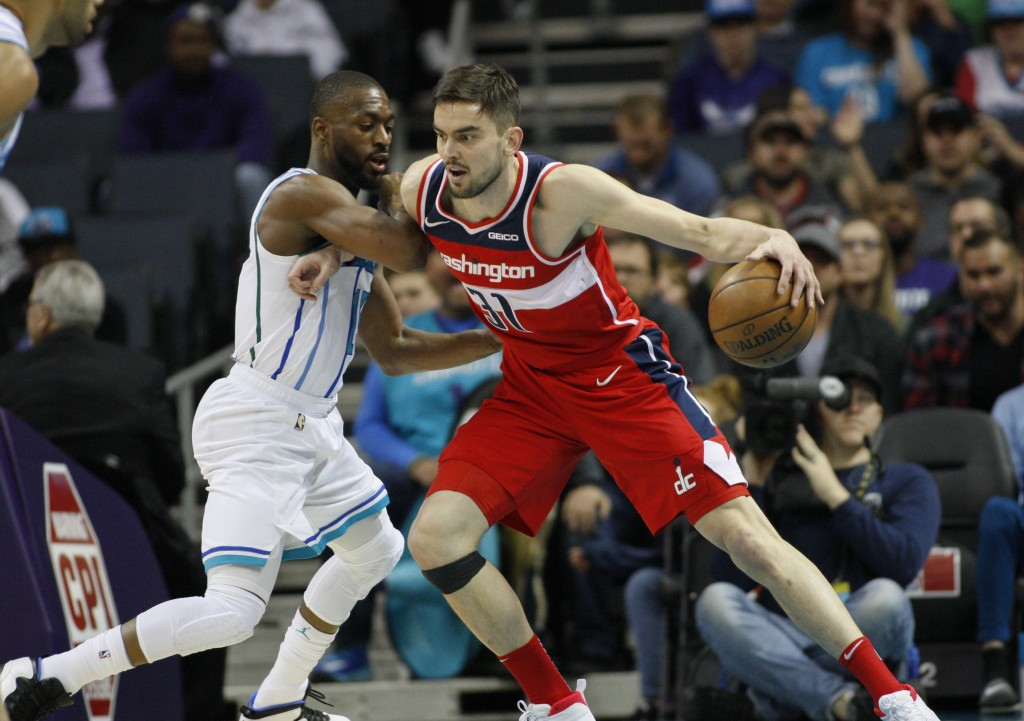 Washington Wizards guard Tomas Satoransky, right, drives into Charlotte Hornets guard Kemba Walker in the first half of an NBA basketball game in Char