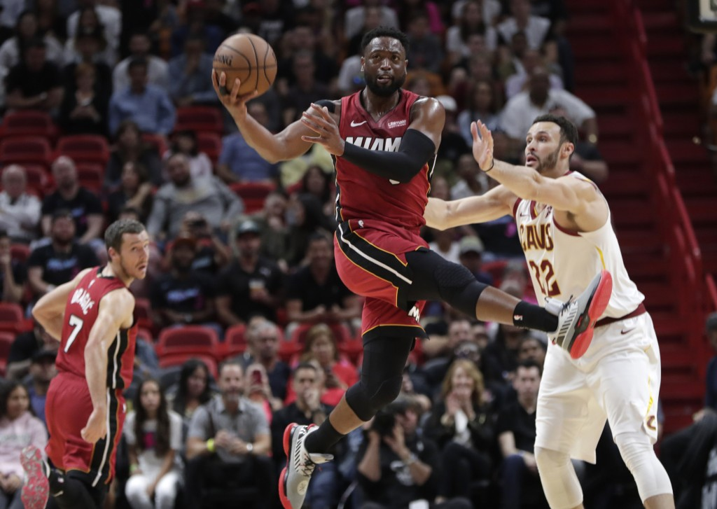 Miami Heat guard Dwyane Wade looks to pass as Cleveland Cavaliers forward Larry Nance Jr. defends during the first half of an NBA basketball game, Fri