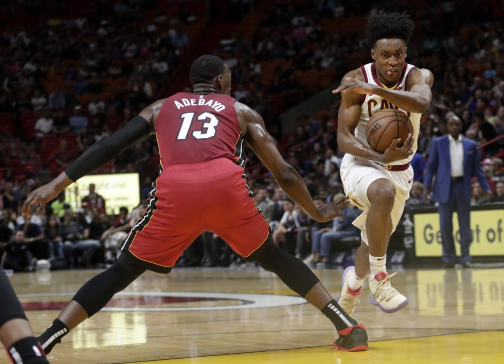 Cleveland Cavaliers guard Collin Sexton, right, drives to the basket as Miami Heat center Bam Adebayo (13) defends during the first half of an NBA bas