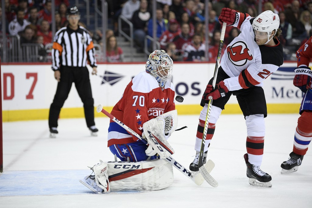 Washington Capitals goaltender Braden Holtby (70) tries to corral the puck, next to New Jersey Devils center Blake Coleman (20) during the first perio