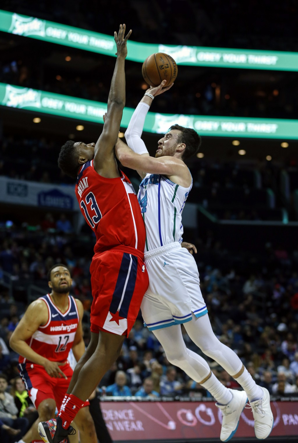 Charlotte Hornets forward Frank Kaminsky, right, shoots over Washington Wizards center Thomas Bryant (13) in the first half of an NBA basketball game