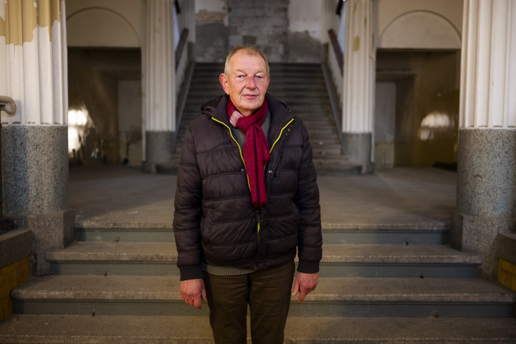 """In this Tuesday, Feb. 22, 2019 photo guide Werner Borchert pose for a portrait in the main entrance of the abandoned """"Haus der Offiziere"""", the headqua..."""
