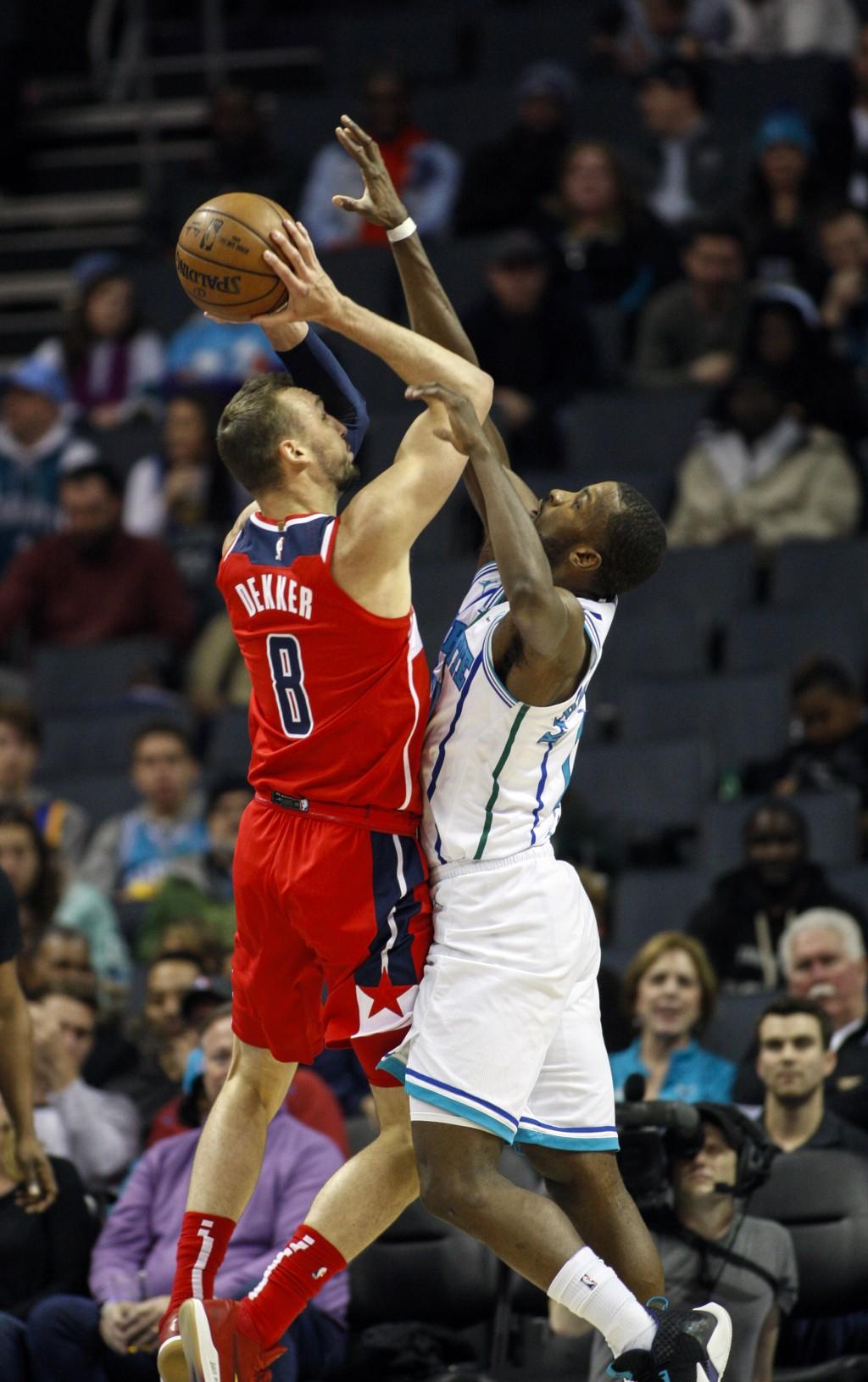 Washington Wizards forward Sam Dekker (8) shoots over Charlotte Hornets forward Michael Kidd-Gilchrist in the first half of an NBA basketball game in
