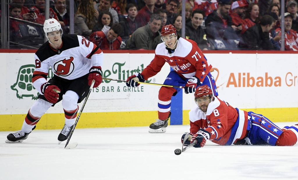 Washington Capitals left wing Alex Ovechkin (8), of Russia, reaches for the near New Jersey Devils defenseman Damon Severson (28) during the first per