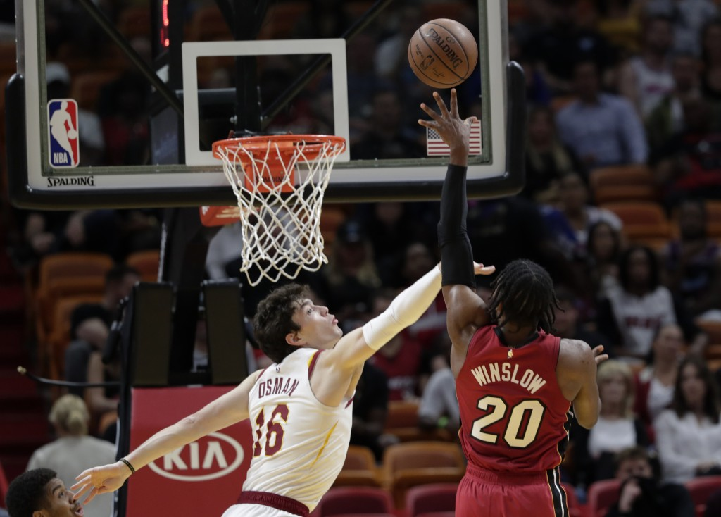 Miami Heat forward Justise Winslow (20) shoots as Cleveland Cavaliers forward Cedi Osman (16) defends during the first half of an NBA basketball game,