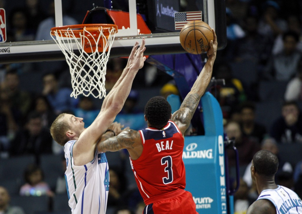 Washington Wizards guard Bradley Beal (3) shoots over Charlotte Hornets center Cody Zeller in the first half of an NBA basketball game in Charlotte, N