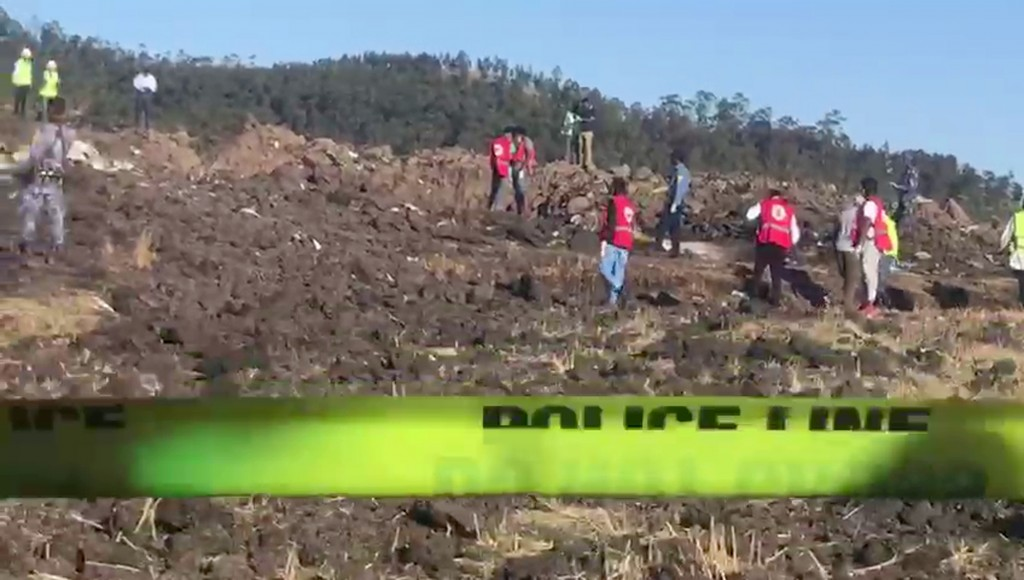 In this image taken from video, rescuers search through wreckage at the scene of an Ethiopian Airlines flight that crashed shortly after takeoff at He...