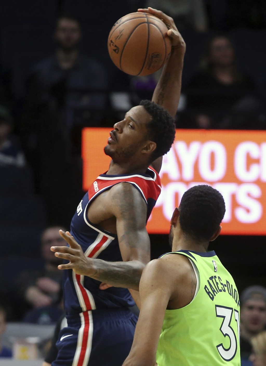 Washington Wizards' Trevor Ariza, left, pulls in a pass as Minnesota Timberwolves' Keita Bates-Diop defends in the first half of an NBA basketball gam...
