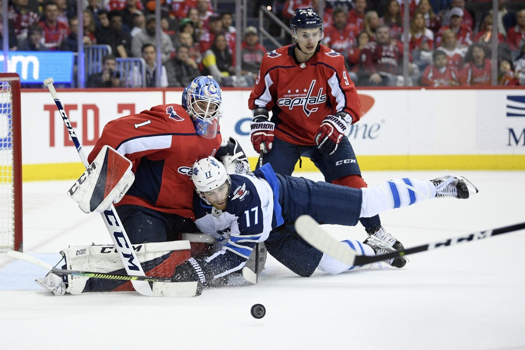 Winnipeg Jets center Adam Lowry (17) collides into Washington Capitals goaltender Pheonix Copley (1) during the second period of an NHL hockey game, S...