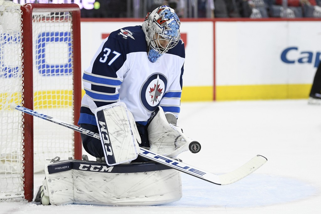 Winnipeg Jets goaltender Connor Hellebuyck (37) stops the puck during the first period of an NHL hockey game against the Washington Capitals, Sunday,
