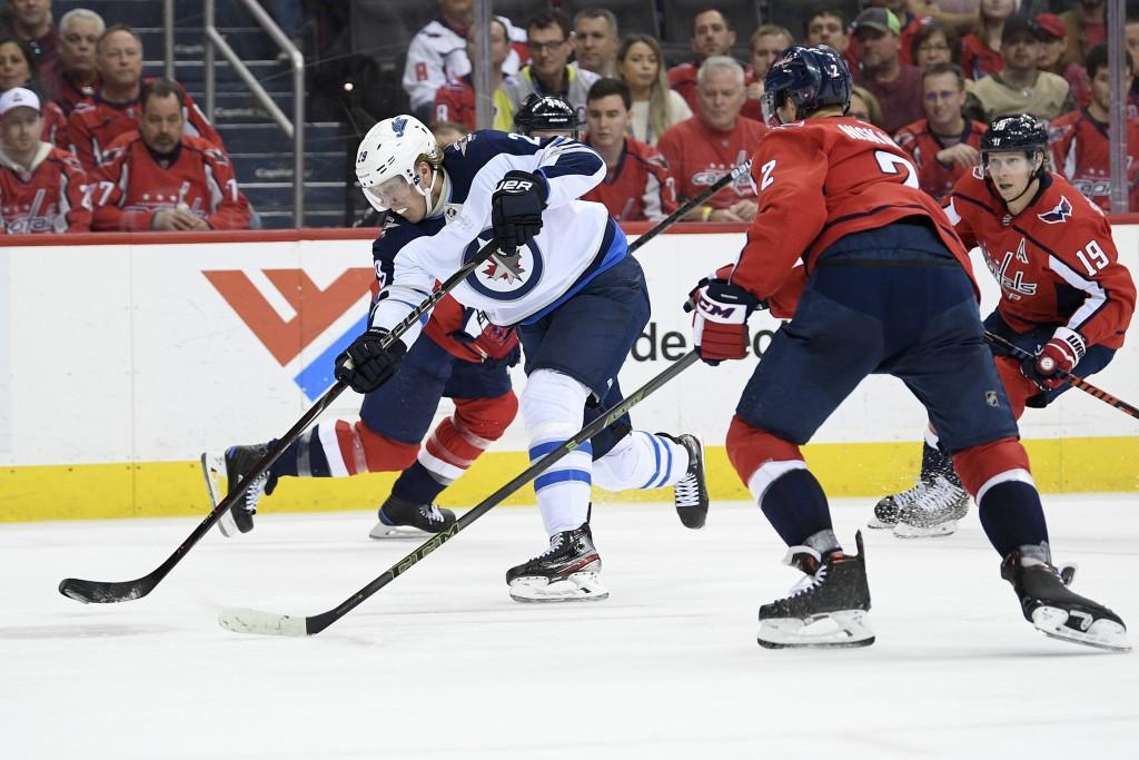 Winnipeg Jets right wing Patrik Laine (29), of Finland, shoots the puck against Washington Capitals defenseman Matt Niskanen (2) and center Nicklas Ba...