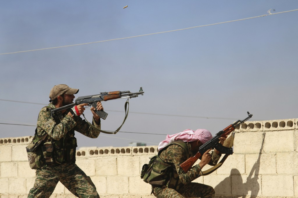 In this Oct. 11, 2015 file photo, Syrian soldiers fire repelling an attack in Achan, Hama province, Syria. Waves of violence in northwestern Syria has