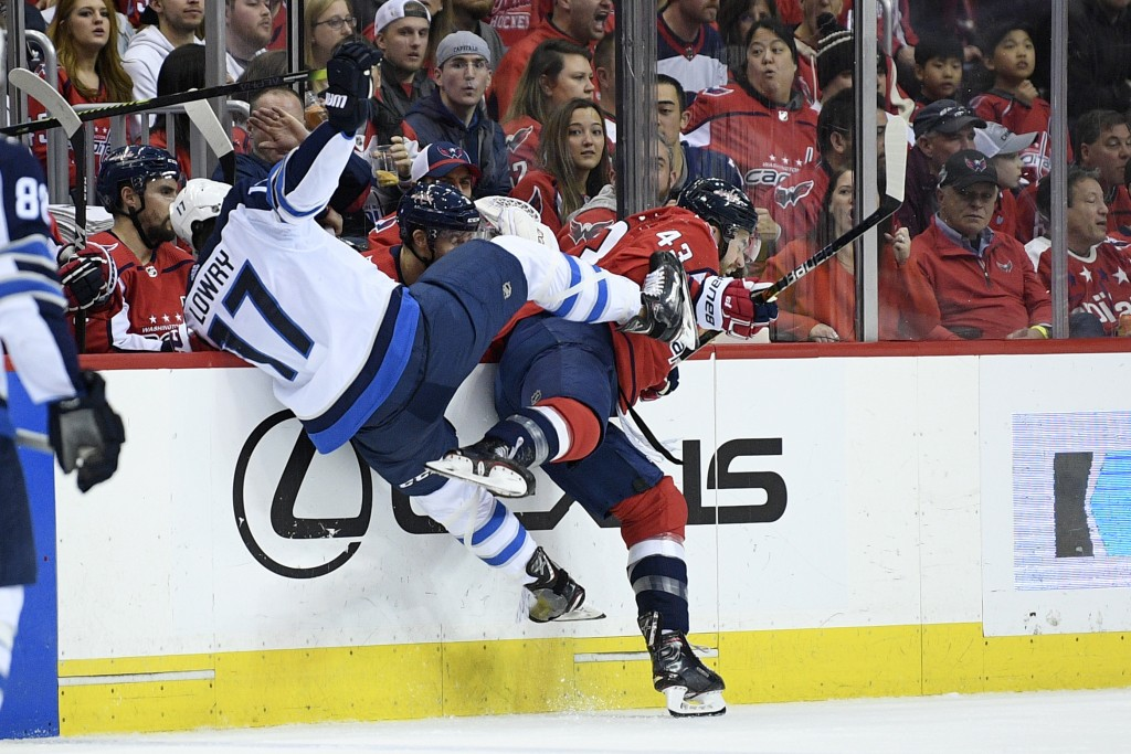 Washington Capitals right wing Tom Wilson (43) and Winnipeg Jets center Adam Lowry (17) collide along the boards during the first period of an NHL hoc