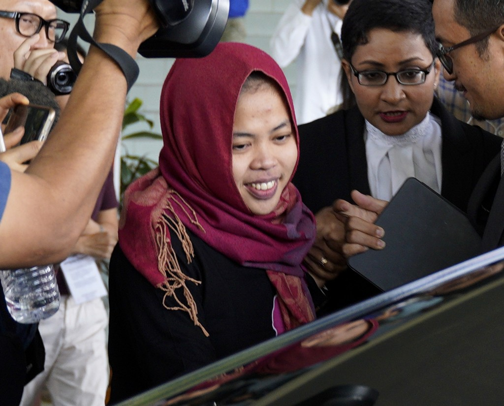 In this March 11, 2019, photo, Indonesian Siti Aisyah, center, smiles as she leaves Shah Alam High Court in Shah Alam, Malaysia. The Indonesian woman