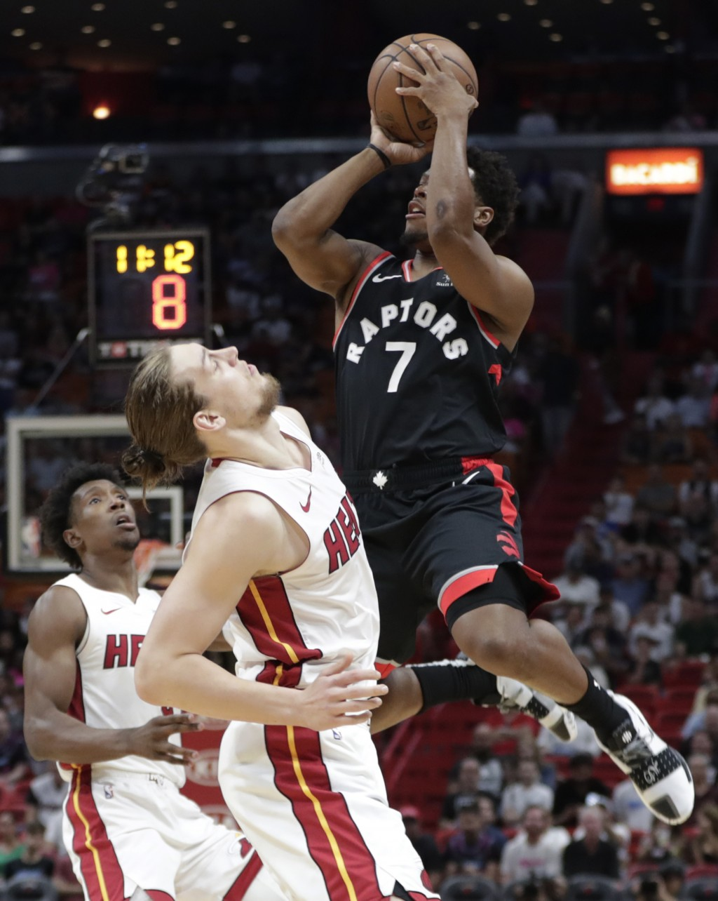 Toronto Raptors guard Kyle Lowry (7) shoots over Miami Heat forward Kelly Olynyk during the first half of an NBA basketball game, Sunday, March 10, 20