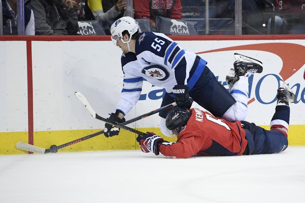 Winnipeg Jets center Mark Scheifele (55) battles for the puck against Washington Capitals defenseman Michal Kempny (6), of the Czech Republic, during ...