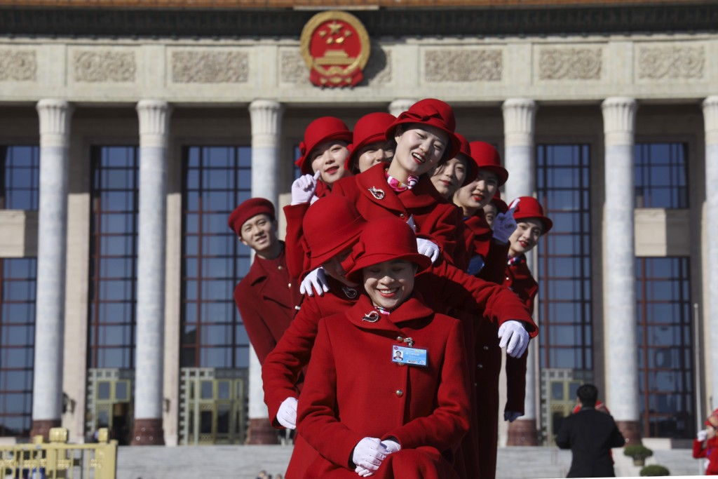 In this March 12, 2019, photo, Chinese bus ushers pose for photos outside the Great Hall of the People during a plenary session of the National People