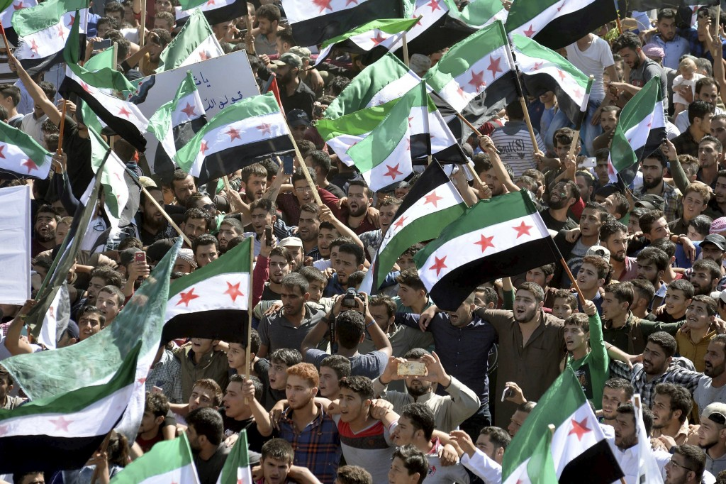 FILE -- In this Sept. 14, 2018 file photo, protesters attend a demonstration against the Syrian government's expected offensive to Idlib, in the north...