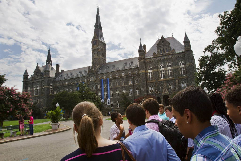 FILE - In this July 10, 2013, file photo, prospective students tour Georgetown University's campus in Washington. Federal authorities have charged col...