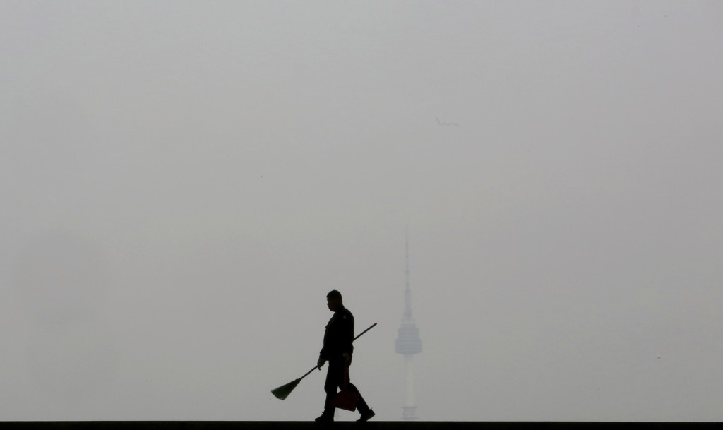 In this March 12, 2019, photo, a worker is silhouetted as the cityscape is covered with a thick haze of fine dust particles, at the National Museum of