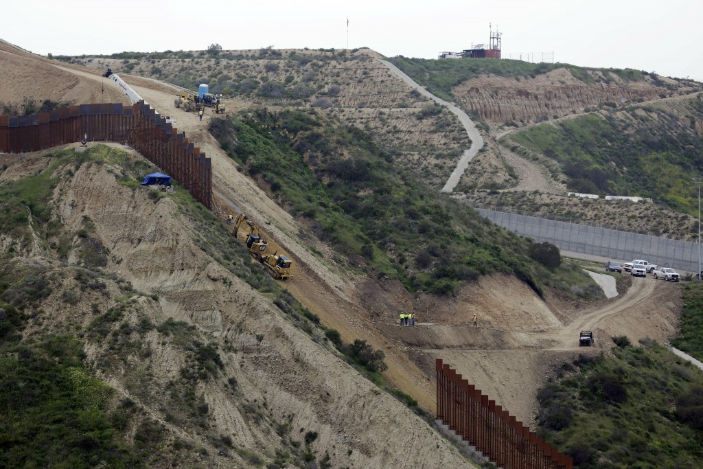 Construction crews replace a section of the primary wall separating San Diego, above right, and Tijuana, Mexico, below left, Monday, March 11, 2019, s